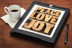 Paix, amour et joie sur un comprimé Photos libres de droits