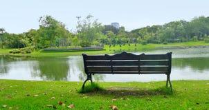 Paix de l'esprit sur le banc vide de jardin sur le coin tranquille de côté de lac Photographie stock