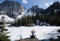 Paix et mindfulness intérieurs La femme méditant sur le rivage scénique de lac avec la belle vue de la neige a couvert des montag image stock