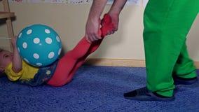 Paizinho brincalhão que puxa sua filha engraçada pelos pés através do tapete no assoalho