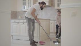 Paizinho com barba e varredura e vácuo bonitos pequenos da filha na cozinha moderna nova com uma vassoura e um pá-de-lixo vídeos de arquivo