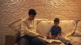 Paizinho com cabelo preto em uma camiseta branca e em um filho pequeno em um azul, listrado, olhar na enciclop?dia, sentando-se e video estoque
