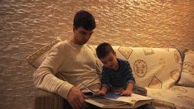 Paizinho com cabelo preto em uma camiseta branca e em um filho pequeno em um azul, listrado, olhar na enciclop?dia, sentando-se e filme