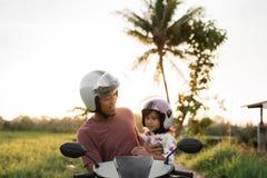 Paizinho com a filha no 'trotinette' da motocicleta imagem de stock royalty free