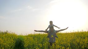 Paizinho com o avião do jogo do menino no campo e a luz solar do fundo, paizinho feliz e filho jogando no parque fora, família video estoque