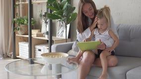 Paizinho da chamada da mamã e da filha na tabuleta na manhã em casa filme