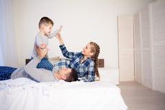 Paizinho da mamã e filho novo na manhã na cama para jogar uma família de riso imagens de stock