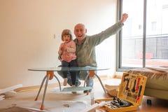 Paizinho e filha que renovam a mesa de centro imagem de stock