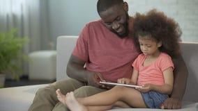 Paizinho e filha que têm o divertimento que joga junto jogos educacionais na tabuleta video estoque