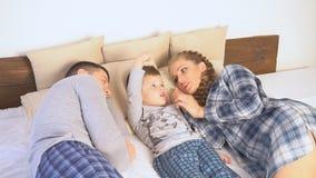 Paizinho e filho da mamã na manhã que encontra-se na cama em casa filme
