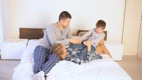 Paizinho e filho da mamã na manhã que encontra-se na cama em casa vídeos de arquivo