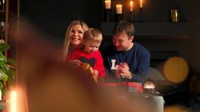 Paizinho e filho da mamã nos presentes abertos do Natal em casa que sentam-se no sofá no interior do Natal Casa morna e acolhedor