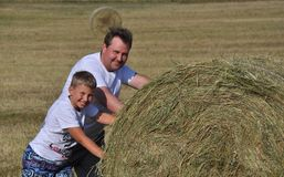 Paizinho e filho perto do monte de feno Foto de Stock Royalty Free