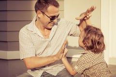 Paizinho e filho que jogam perto de uma casa imagens de stock royalty free