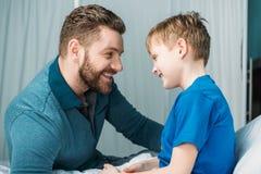 Paizinho e filho que olham se na câmara do hospital foto de stock
