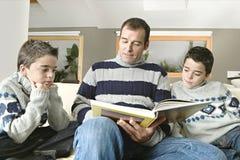 Paizinho e livro de leitura dos miúdos Foto de Stock