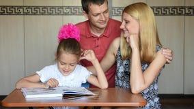 Paizinho e mamã que olham lovingly meu primeiro-graduador da filha vídeos de arquivo