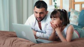 Paizinho e portátil bonito do uso da criança que encontram-se na cama, jogo online dos jogos, movimento lento