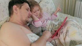 Paizinho e pouca filha na cama que joga na tabuleta video estoque