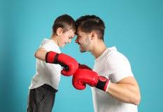 Paizinho e seu filho com luvas de encaixotamento fotografia de stock