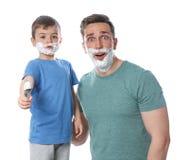 Paizinho e seu filho pequeno com rapagem da espuma nas caras fotos de stock royalty free