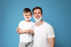 Paizinho e seu filho pequeno com rapagem da espuma nas caras foto de stock royalty free