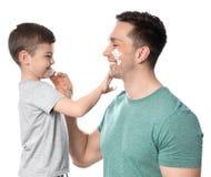 Paizinho e seu filho pequeno que aplicam-se barbeando a espuma fotos de stock royalty free