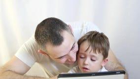 Paizinho e seu filho que jogam em uma tabuleta em um fundo branco O conceito de uma família feliz vídeos de arquivo