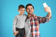 Paizinho e seu filho que tomam o selfie foto de stock