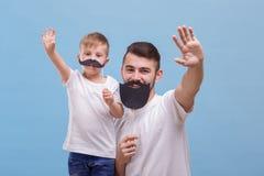 Paizinho e seu olá! de ondulação do filho em um fundo azul imagens de stock