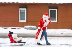 Paizinho em um terno de Santa Claus e seu filho pequeno que monta o pequeno trenó sob a neve do inverno, na rua da vila Foto de Stock Royalty Free