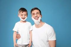 Paizinho engraçado e seu filho pequeno com rapagem da espuma nas caras imagem de stock royalty free