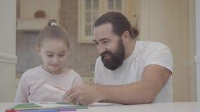 Paizinho farpado e uma pintura pequena bonita da filha com os flamasters que sentam-se em uma tabela em um dia livre Pai do passa vídeos de arquivo