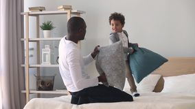 Paizinho feliz e filho africanos que têm a luta de descanso na cama vídeos de arquivo