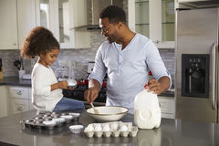 Paizinho preto e filha nova que cozem junto na cozinha fotografia de stock royalty free
