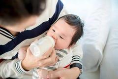 Paizinho que alimenta seu infante da filha do bebê do bebê adorável da garrafa com uma garrafa de leite imagem de stock royalty free