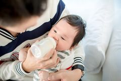 Paizinho que alimenta seu infante da filha do bebê do bebê adorável da garrafa com uma garrafa de leite fotografia de stock royalty free