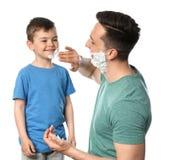 Paizinho que aplica-se barbeando a espuma na cara do filho foto de stock royalty free