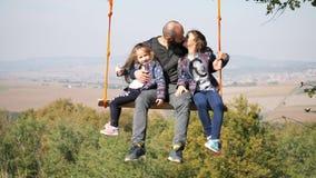 Paizinho que balança com filhas em um balanço sob uma árvore vídeos de arquivo
