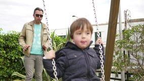 Paizinho que empurra seu bebê no balanço do parque