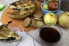 Paj, en skiva av äppelpajen med körsbäret och valnötter, en kopp te, äpplen i en korg, valnötter och kakor på tabellen royaltyfri foto