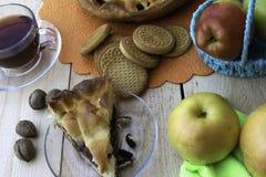 Paj, en skiva av äppelpajen med körsbäret och valnötter, en kopp te, äpplen i en korg, valnötter och kakor på tabellen arkivfoton