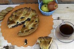 Paj, en skiva av äppelpajen med körsbäret och valnötter, en kopp te, äpplen i en korg, valnötter och kakor på tabellen royaltyfria foton