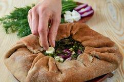 Paj med spenat, fetaost, lökcirklar på trätabellen Förbereda den vegetariska pajen Arkivbild