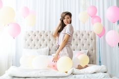 Pajama party. Attractive young smiling woman in pajama in the bedroom. stock photos