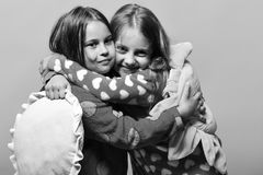 Pajama party and childhood concept. Girls with loose hair hug. Kids with smiling faces. Pajama party and childhood concept. Girls with loose hair hug each other stock images