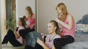 Pajama party girlfriends. Two young women relaxing at home, enjoying the tablet, braid hair. Two young women relaxing at home, enjoying the tablet, braid hair stock video