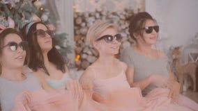 Pajamaparti flickor i pyjamas som har gyckel nära en julgran arkivfilmer