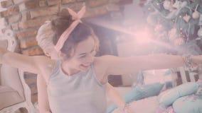 Pajamaparti flickor i pyjamas som har gyckel nära en julgran stock video
