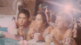 Pajamaparti flickor i pyjamas som har gyckel nära en julgran lager videofilmer